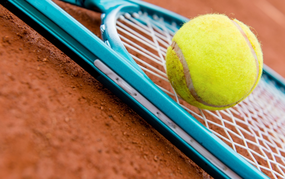 Tennis racket with a ball at the clay court