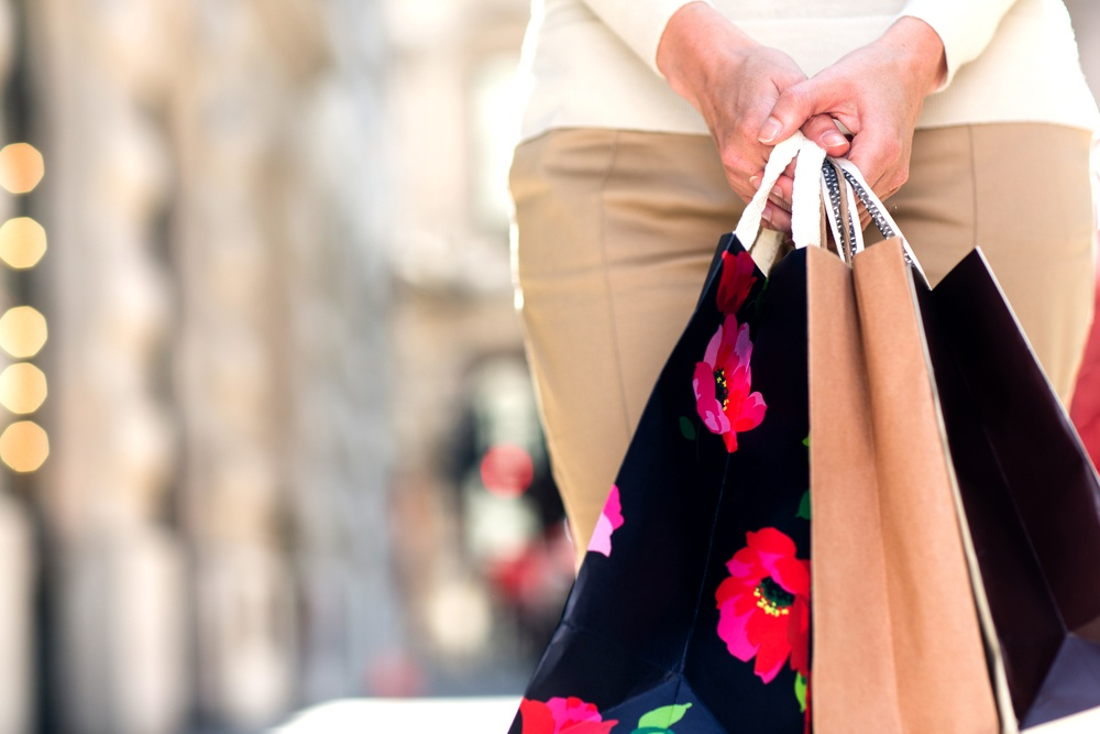 Unrecognizable female shopper holding three shopping bags